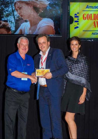 """Bei der Preisverleihung: Gary Slade (Amusement Today) übergibt Michael Mack, Geschäftsführung Europa-Park, in Begleitung seiner Ehefrau Miriam Mack, den """"Golden Ticket Award"""". Bild: Europa-Park"""
