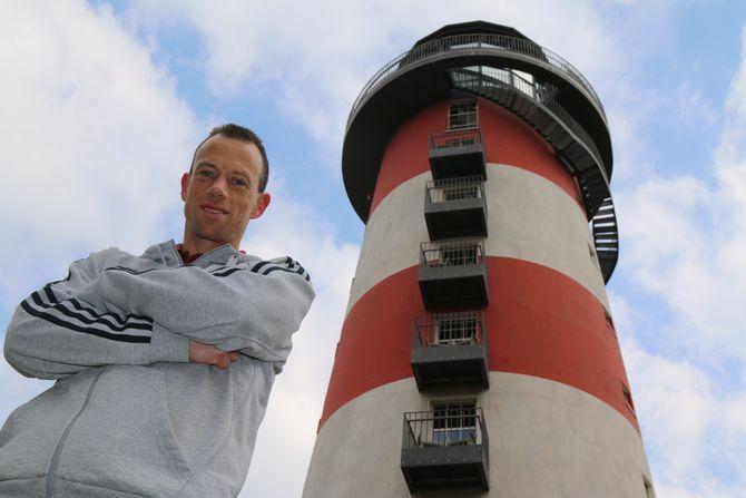 "Up to the top! André Weinand vor dem Leuchtturm des 4-Sterne Superior Hotels ""Bell Rock"" des Europa-Park. Bild: Europa-Park"