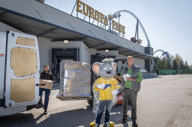 Roland Mack und Ed Euromaus übergeben die Regen-Ponchos an Eugen Burulea, der die Spende ins Elsass bringt. Bild: Europa-Park