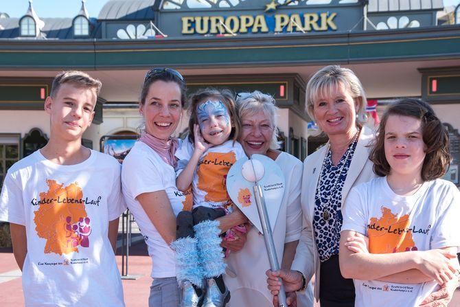 Die kleine Mila brachte am Welthospiztag gemeinsam mit ihrer Familie das Wahrzeichen des Kinder-Lebens-Laufs zu Sabine Kraft (3.v.re.) und Mauritia Mack (2.v.re.) in den Europa-Park. Bild: Europa-Park