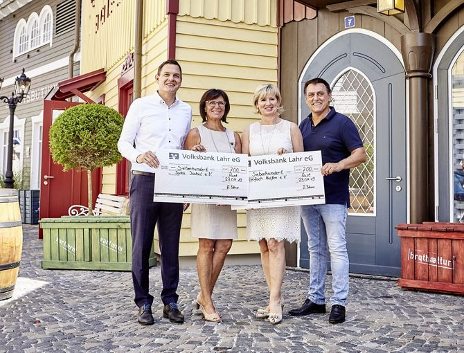 Andreas Sehrer (li.) und Armin Kienzler (re.) des SV Rust übergeben die Spendenschecks an Marianne und Mauritia Mack. Bild: Europa-Park