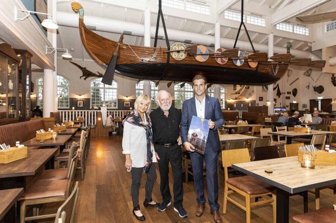 """Burghard Pieske (Mitte) mit seiner Frau Silke Pieske sowie Thomas Mack beim Besuch des Museumshotels """"Krønasår"""". Das Holzschiff """"Wiking Saga"""" prägt das Ambiente des Restaurants """"Bubba Svens"""". Bild: Europa-Park"""